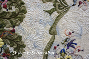 a picture of Sharon Schamber's quilt with a close up showing her fine stitches and turned edge applique