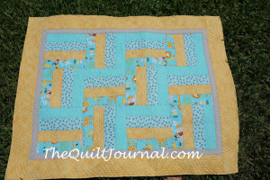 picture of finished baby quilt showing free motion quilting ruler work