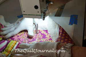 a picture of me working with the ruler at a 90 degree angle, changing my hand position after passing the half-way point to maintain pressure/control on the ruler during free motion quilting ruler work