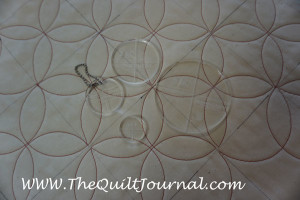 A picture of circle templates by TCR Engraving and graphics used to free motion quilt the orange peel motif in background