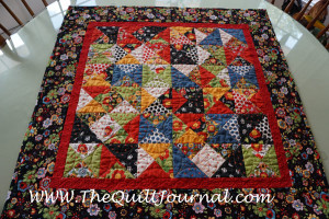 a picture if a scappy table topper with orange peel quilting on it