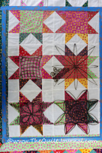 a picture of a quilt topper with Plexiglas on top with doodles to figure out free motion quilting design options
