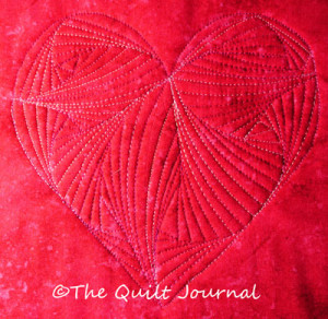 a picture showing a free motion quilting twisted design in a heart stitched with Floriani 40 wt polyester variegated