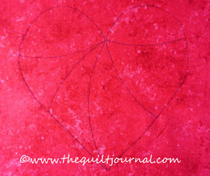 a picture of a heart drawn on frabic that has lines drawn showing the segments that will later become a free motion quilting twisted design