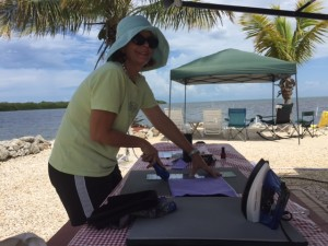 A picture of me cutting quilt fabric using a rotary cutter at our camsite in the Florida Keys