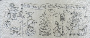 a close up picture of a free motion quilting Halloween table runner