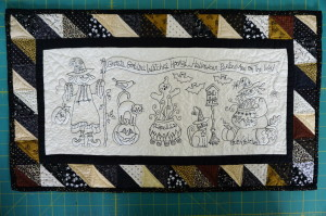 A picture of Bird Brain Designs WITCHES HOORAY TABLE RUNNER free motion quilting Halloween table runner