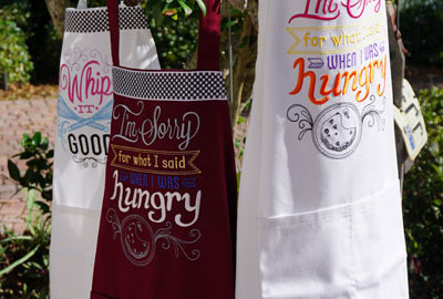 """a picture if 3 aprons with Urban threads """"spice it up designs embroidered on them"""